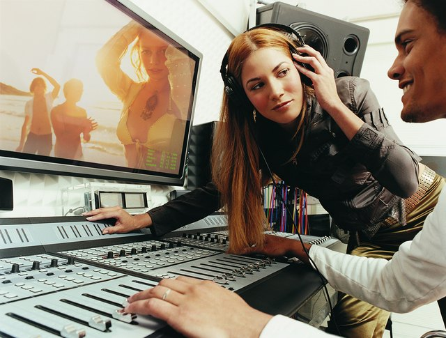 pop musician listening to music on her headphones in a recording studio as a producer watches - Executive Producer Music