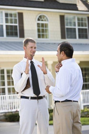Two men talking in street outside house