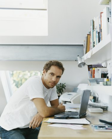 Serious Looking man Sits at his Desk With a Laptop in Front of him