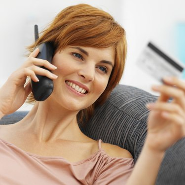 Close-up of young woman talking on mobile phone and holding credit card