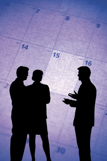 Composite of silhouette of businesspeople and calendar