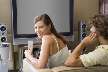 Couple watching LCD TV with surround sound speakers