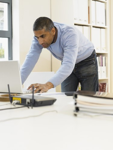Man standing by desk using laptop computer