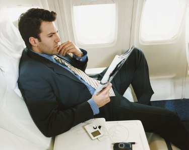 Businessman Sitting in an Aircraft Reading a Magazine