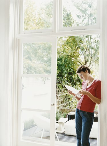 Woman Stands By an Open Patio Door Examining a Document