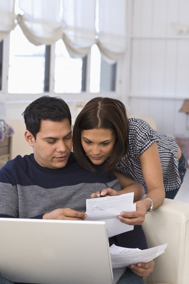 couple paying bills on computer