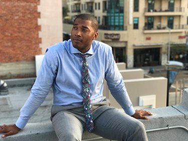Young Black man in business clothes sitting on a rooftop