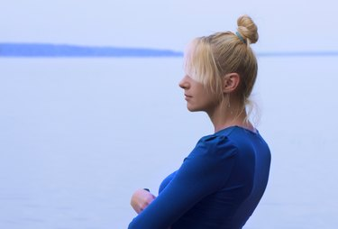 Blond woman in blue top looking out over water