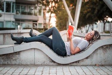 a millennial woman reading a book in a city public park