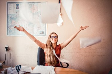 Woman at desk tossing papers in the air