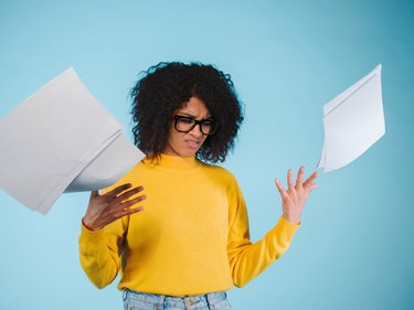 Angry young afro american businesswoman or student is scattering documents on blue background