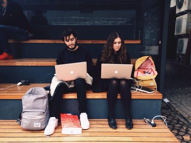 Two people on laptops sitting next to each other on bleachers