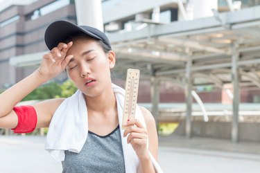 Dehydrated athlete holding thermometer in heat