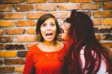 Woman screaming into screaming woman's ear