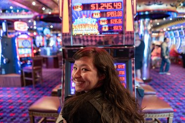 Young woman smiling while seated in front of winning slot machine