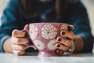 Hands cupping a large coffee mug