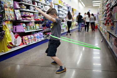 boy hula hooping in the aisle of a dollar store