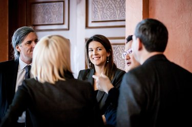Woman smiling amid colleagues all in business suits