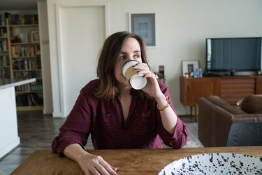 Young millennial woman drinking and holding a coffee cup