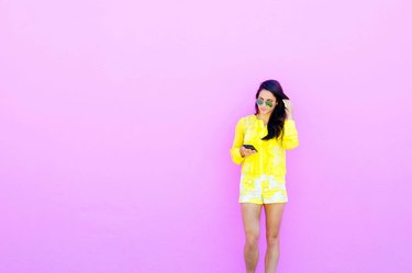 Young woman in yellow outfit standing against purple wall