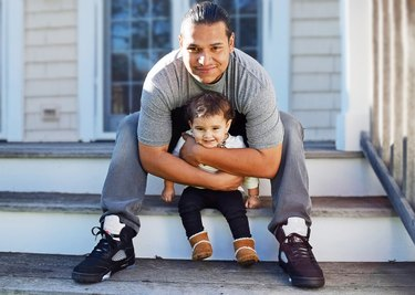 Happy Hispanic Dad and daughter sharing a loving moment outside on the steps of their house