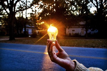 Unseen person holds lightbulb in front of setting sun outdoors