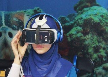 Young hijabi in aquarium wearing VR headset