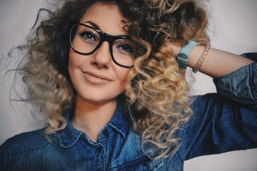 Young woman with curly hair posing with glasses