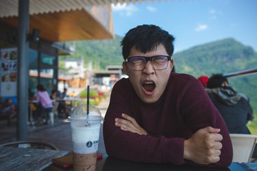 Young East Asian man yawning at outdoor cafe