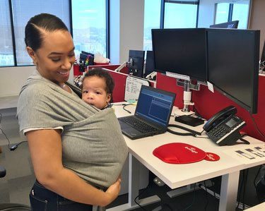 Young Black mother wearing an infant in a sling in an office