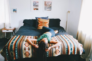 Young Black woman relaxing on bed in furnished room