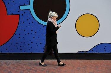A happy millennial girl walking alongside a mural using her mobile phone