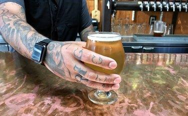 Hipster bartender serves a beer in a glass at a colorful bar