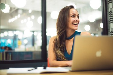 White woman smiling at laptop in modern office setting