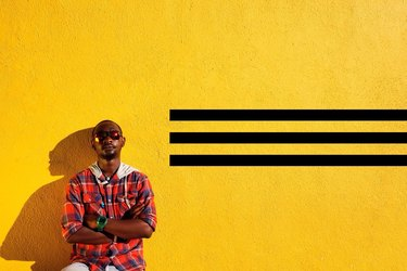 Young Black man standing in front of yellow concrete wall