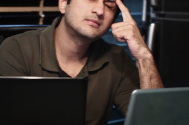 Young South Asian man stressed out in front of laptops