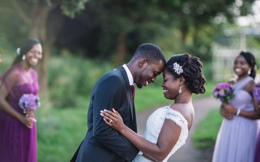 Young Black bride and groom looking joyous at outdoor wedding