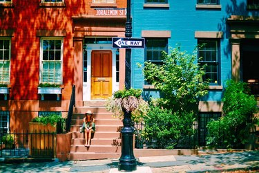 Woman sitting on stoop in front of brightly painted Brooklyn brownstones