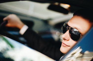 White man in suit and sunglasses driving a car
