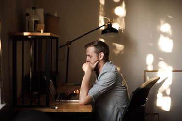 Young white man working on laptop in sunny home office