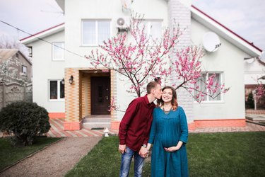 Young white couple standing in front of new house and blossoming tree