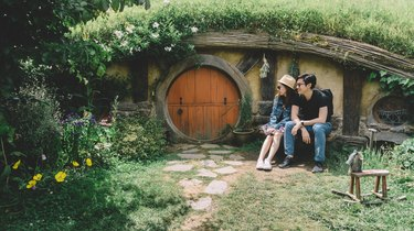 Couple sitting in front of hobbit house