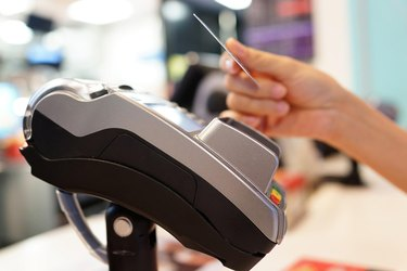 Hand holding credit card near checkout payment terminal