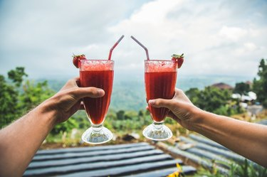 Two hands holding red smoothies in front of tropical vista