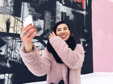 Young woman in pink coat taking selfie against pink wall