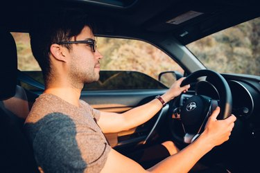Young man wearing sunglasses driving a car