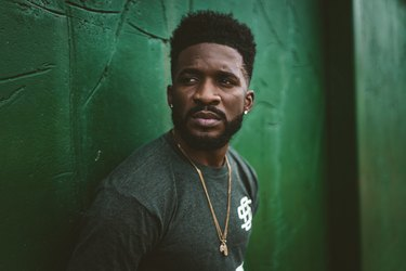 Athletic Black man with beard looking worried in front of green wall