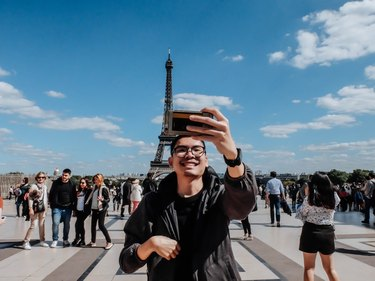 Young man takes selfie in front of the Eiffel Tower, Paris