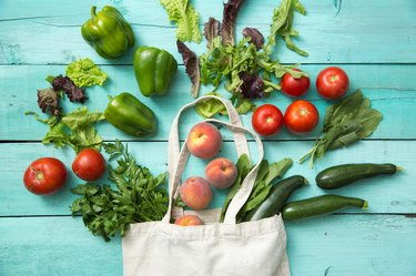 Artfully arranged produce and reusable grocery bag