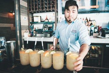 Bartender serving five cocktails at bar